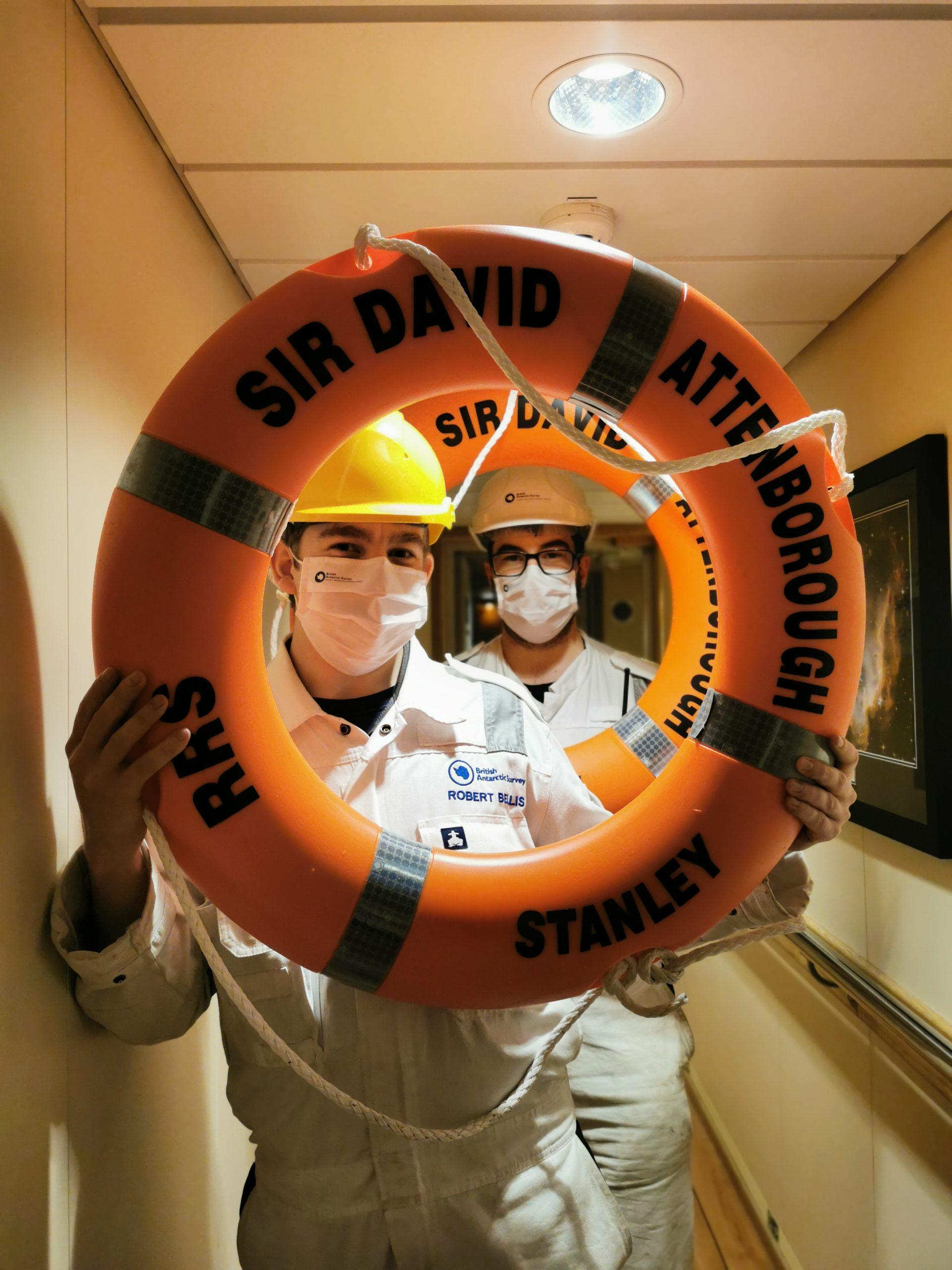 Two men in hard hats poke their faces through an orange life ring