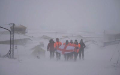 A group of people walking across snow covered ground, holding a flag