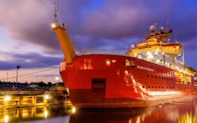 A large red ship in water. It is dark and the ship is lit up.